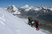 Petra und Jörg auf den letzten Metern zum Gipfel des Breithorn. Im Hintergrund Matterhorn und Dent Blanche.